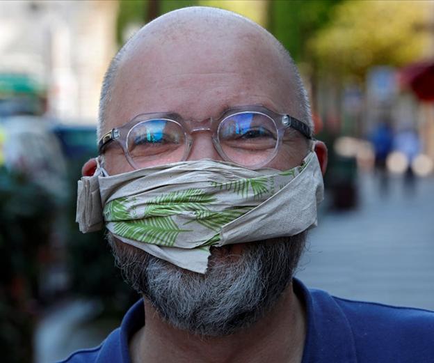 Un bărbat purtând o mască din șervețel. THOMAS COEX/Getty Images