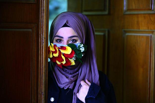 O femeie care poartă o mască cu petale de trandafir. HAIDAR HAMDANI/Getty Images